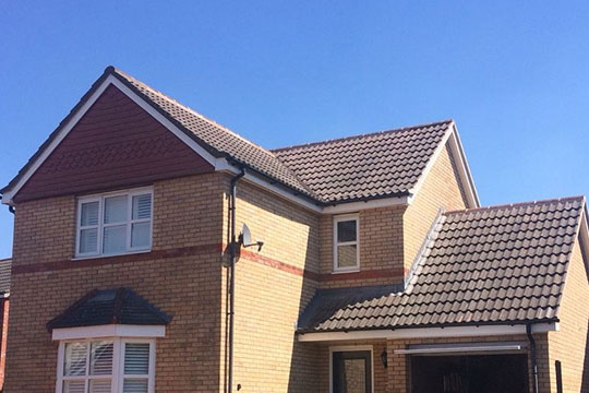 An image fo a large detached house with a pitched roof, laid by AES Roofing Contractors.