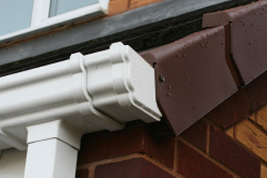 An image of a white, PVC guttering system installed on a house.