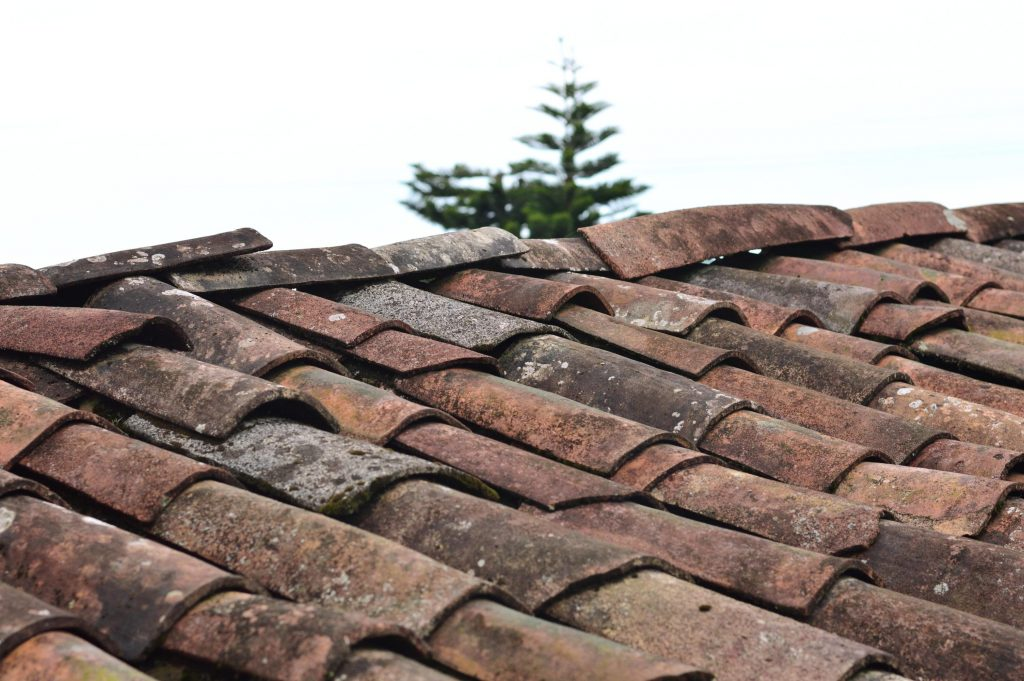 An image of a roof with tiles that are out of place and need repairing.