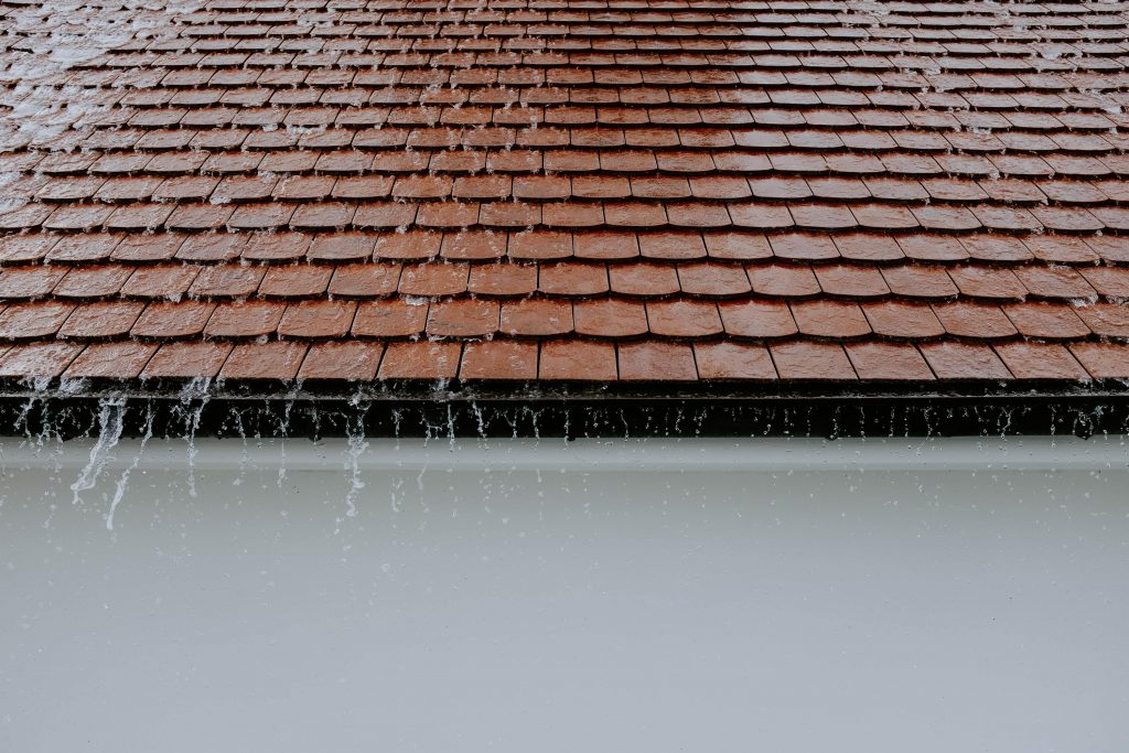 An image of the rain coming down on a pitched roof.